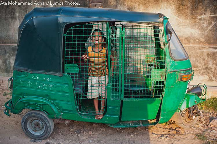 The taxi driver's son plays inside his dad's taxi